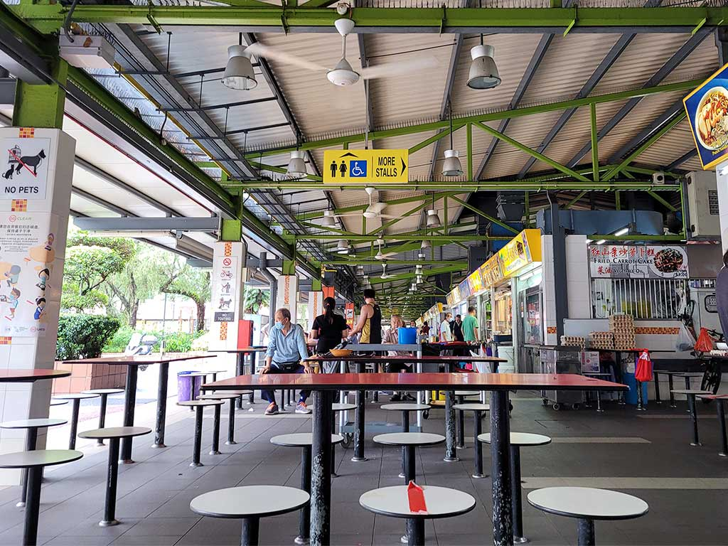 Socially distanced hawker center with iconic crossed out seats reminding you of 2020