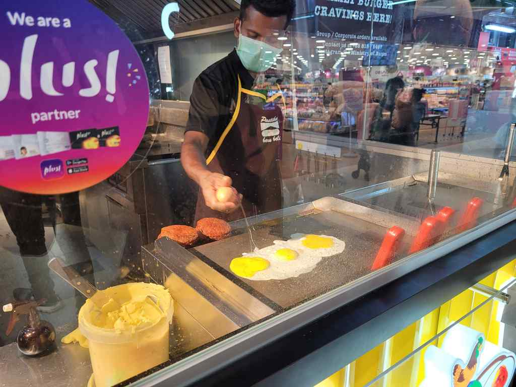 Ramly chef preparing your burgers in front of you, starting with the egg staple